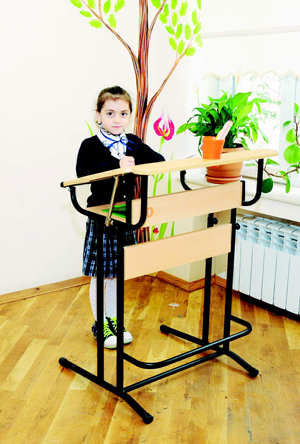 Девочка работает стоя за конторкой