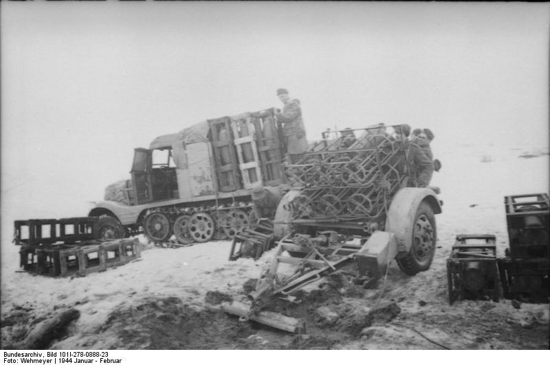 Транспортёр боеприпасов и пусковая установка 28/32 cm Nebelwerfer 41. Справа мины в транспортной укупорке.