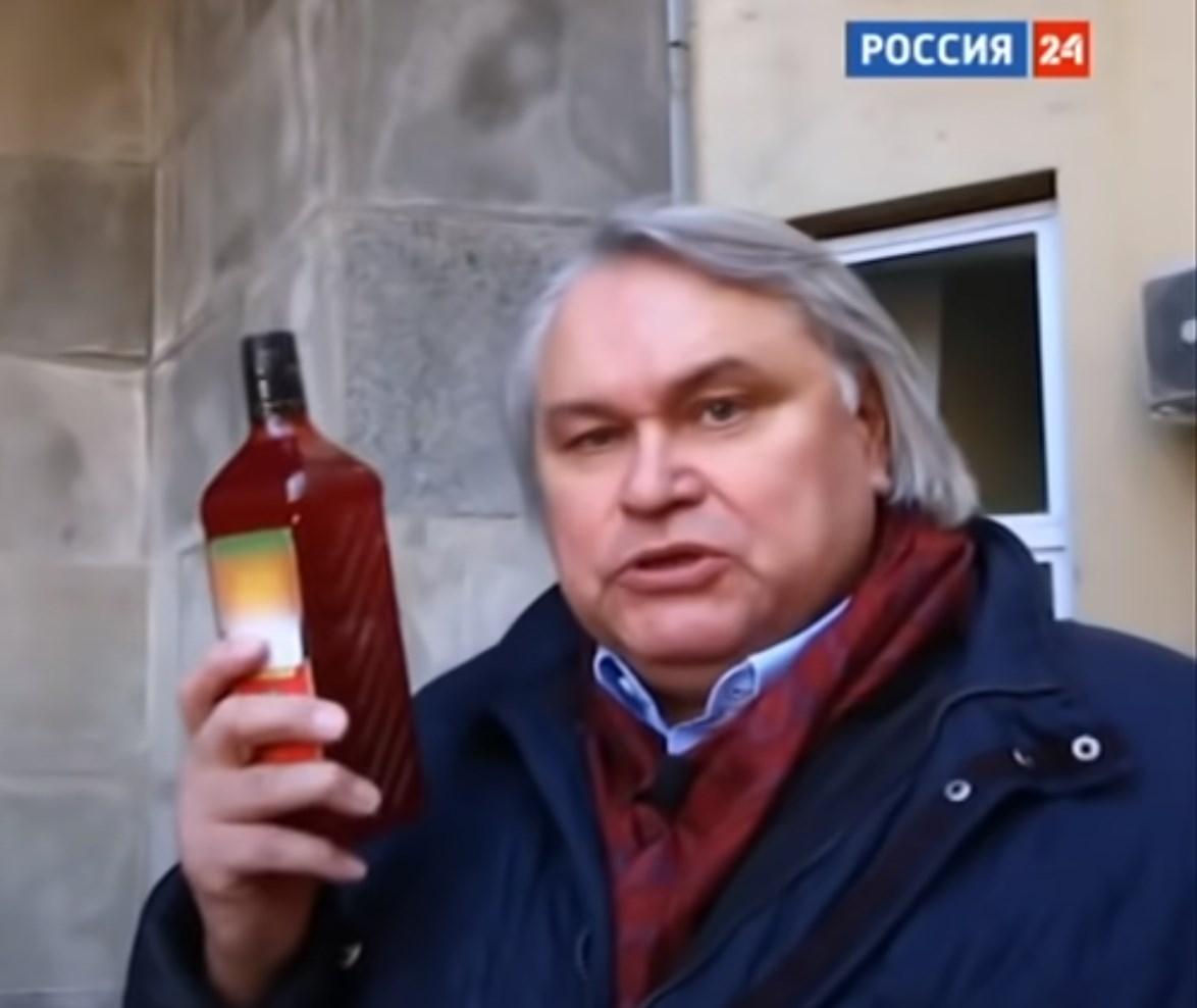 Журналист А.Мамонтов с бутылкой красного пальмового масла.