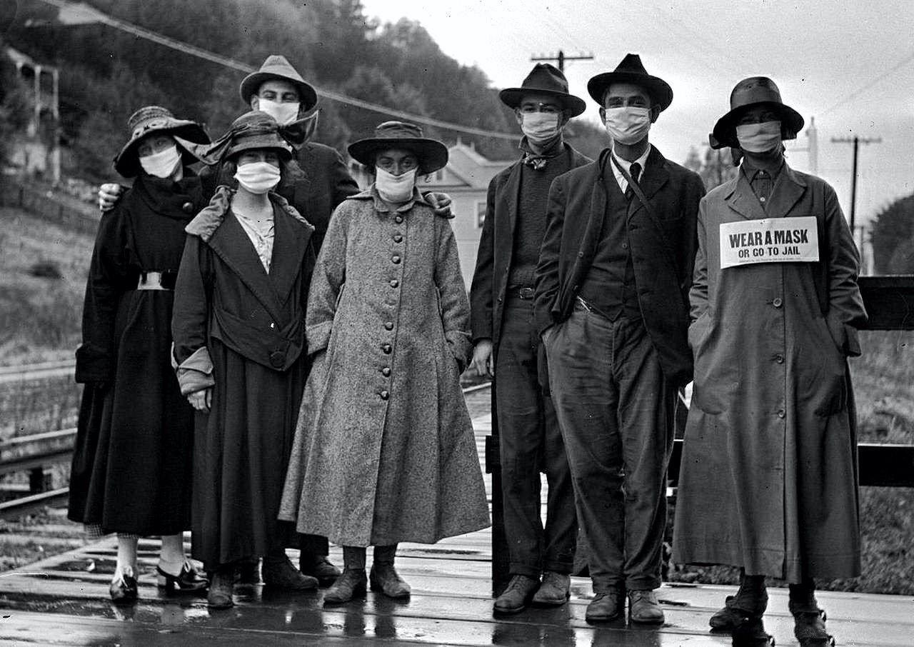 """Надпись под фотографией 1918 года: """"Надень маску или отправляйся в тюрьму""""."""