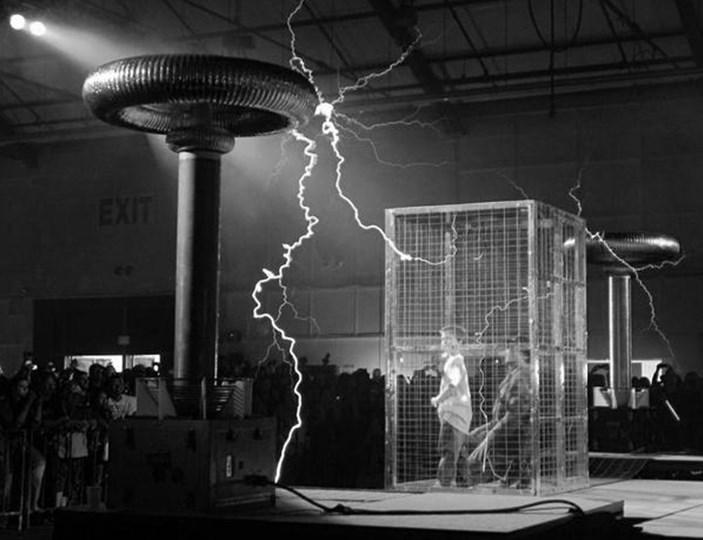 Слева трансформатор Николы Тесла, вырабатывающий напряжение в сотни тысяч Вольт, справа клетка Фарадея с людьми внутри.